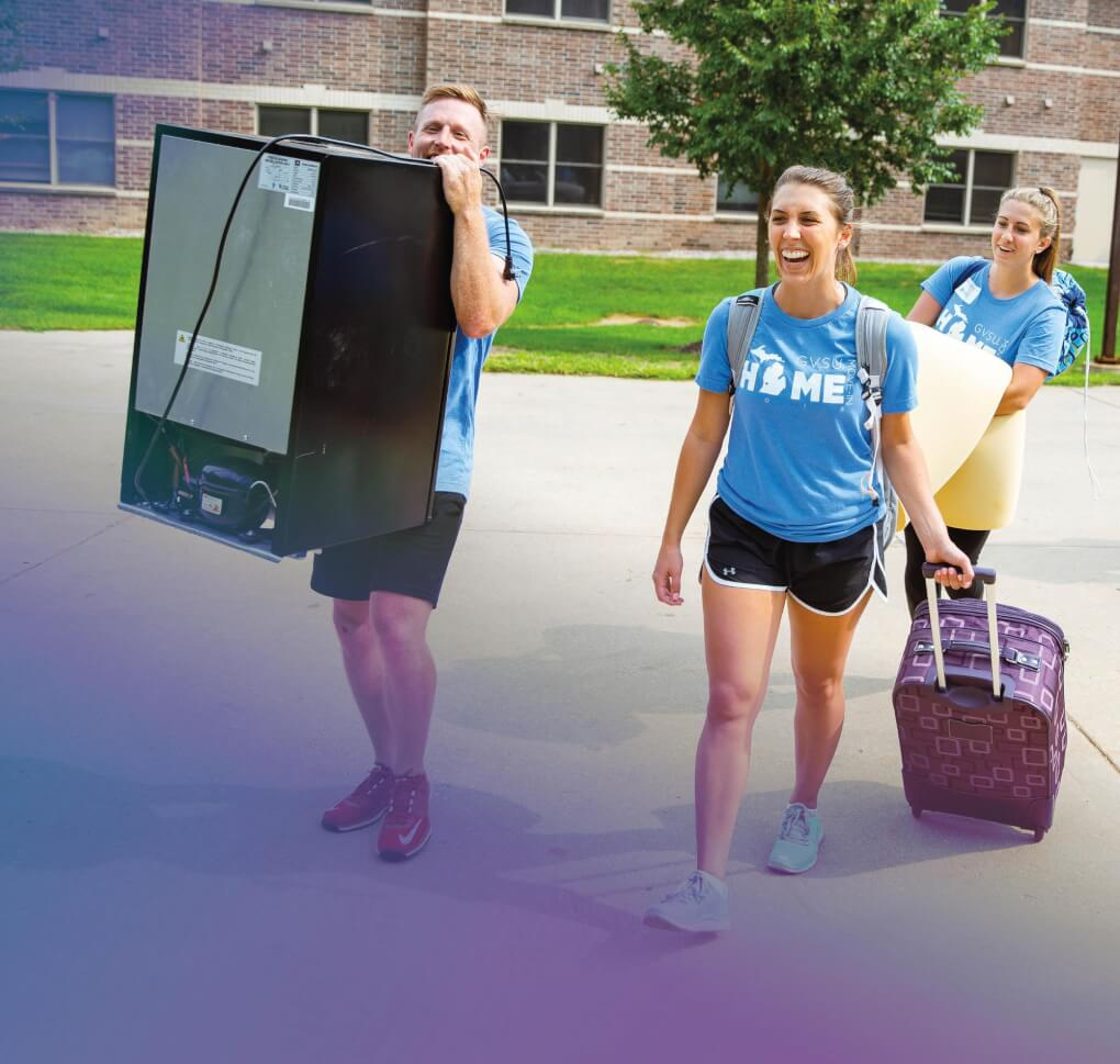 Alumni carrying suitcases and fridges during movein